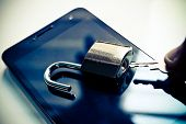 picture of theft  - hand with a key trying to open security lock on a smartphone  - JPG