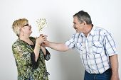 Middle Aged Man Giving Flowers To His Wife