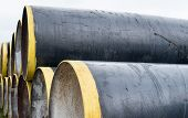image of orifice  - Stack of new metal pipes with yellow - JPG