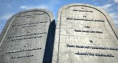 stock photo of ten  - Two stone tablets with the ten commandments inscribed on them standing in brown desert sand infront of a blue sky - JPG
