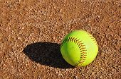 stock photo of softball  - Yellow Softball Sitting on the Infield Dirt - JPG