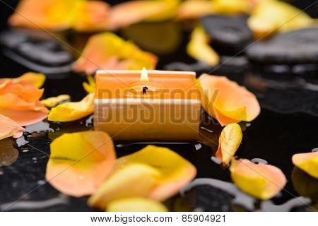 Set of orange rose petals with candle and therapy stones