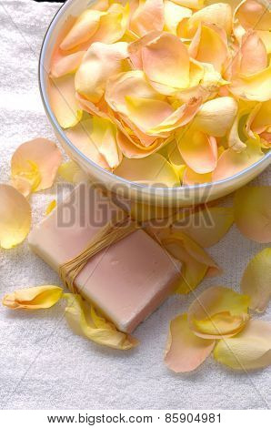 Soap and rose petals in bowl on towel