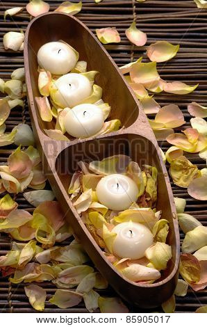 rose petals with candle in wooden bowl on bamboo mat