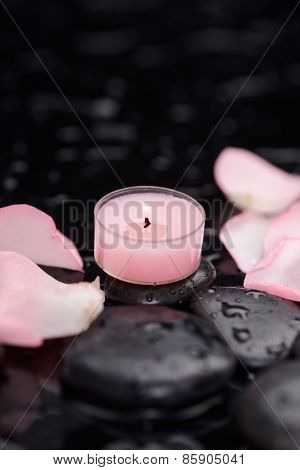 Still life with pink rose petals with pink candle and therapy stones