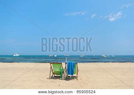 Beach with empty chairs in green and blue