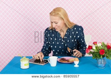 Mature woman reading news on digital tablet in the morning while having breakfast