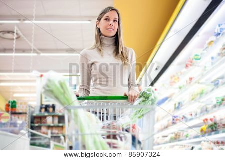 Woman pushing a shopping cart in a grocery store