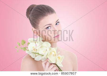 Portrait Of Young Beautiful Woman With Orchid Flower Over Pink