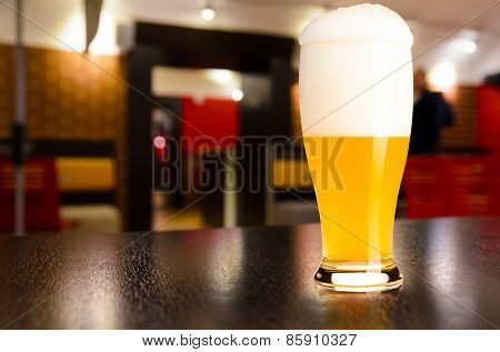 glass of fresh draft weiss beer on table in pub