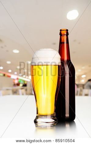 glass and bottle of fresh draft unfiltered beer on table in cafe