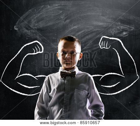 school boy is standing with strong hands on blackboard behind him
