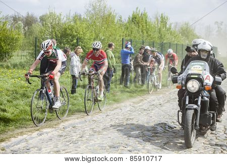 The Peloton On A Cobblestoned Road