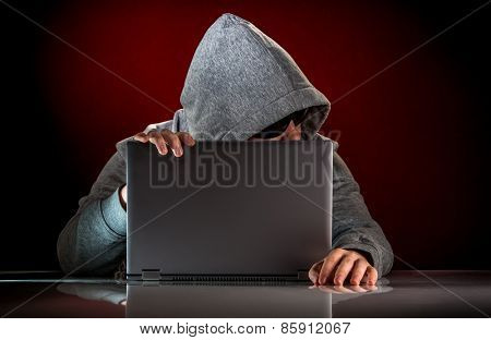 Hacker in a sunglasses with laptop.