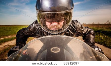 Biker in helmet and leather jacket racing on the road