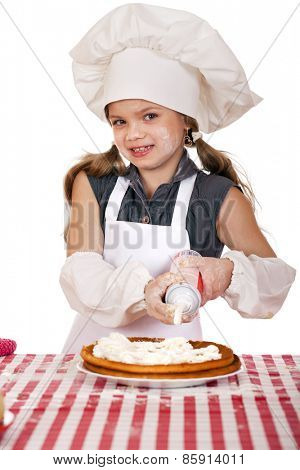 Beautiful happy seven year old girl in chef uniform with shortcakes and whipped cream, studio on white background