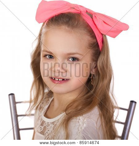Portrait of a little girl with a red bow on her head, studio on white background