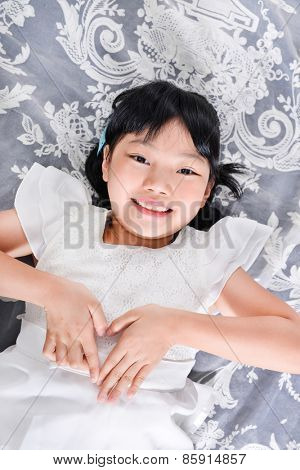little girl laying on in bed with hands gesture