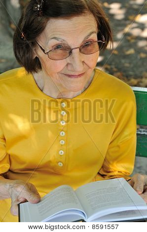 Senior Woman Reading Book Autdoors