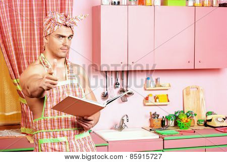 Handsome muscular man in an apron studies a cookbook in the pink kitchen. Love concept. Valentine's day. Women's day.