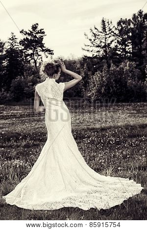 Beautiful graceful bride in a summer park. Wedding dress and accessories. Black-and-white photo.