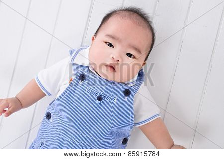 The baby lays. Age of 8 months. It is isolated in studio