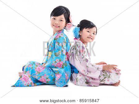 little girl wearing kimono sitting back to back isolated