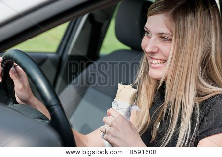 Portrait Of Young Woman Eating While Driving Car
