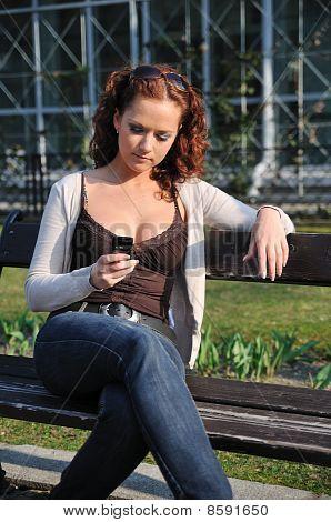 Junge Frau auf der Bank In Handy eingeben