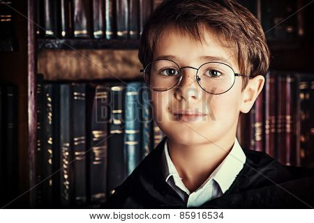 Smart boy stands in the library by the bookshelves with many old books. Educational concept. Science. Vintage style.