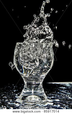 Ice Splashing Into A Glass On White