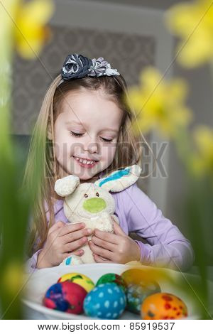 Smiling cute child with easter eggs and plush bunny. Easter