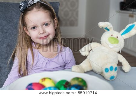 Smiling cute kid with easter eggs and plush bunny. Easter
