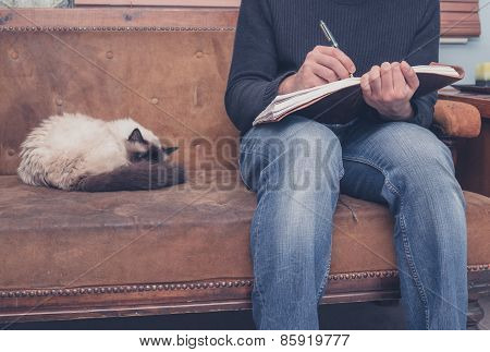 Man Sitting On Sofa Writing Ion Notebook