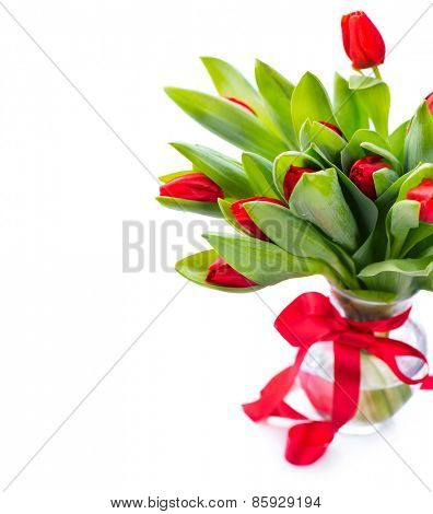Spring Tulip Flowers bouquet in a vase over white. Mother's Day or Easter Tulips bunch decorated with red satin ribbon. Floral Border Design. Isolated on a white background