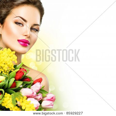 Beauty model Woman with Spring Flower bouquet. Beautiful girl with a Bunch of colorful Tulip flowers. Happy surprised model woman smelling flowers. Mother's Day. Springtime