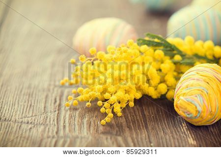 Easter Background. Beautiful Easter holiday border decorated with colourful eggs and mimosa flowers. Springtime. Invitation card design with space for your text