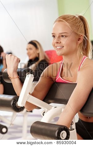 Smiling young woman working out at the gym on exercise machine.