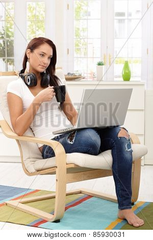 Pretty girl enjoying leisure time with laptop and a cup of tea in living room armchair.