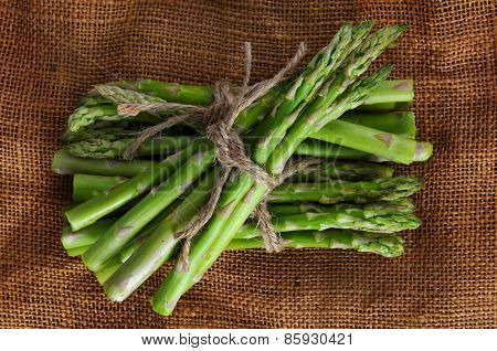 Bunches of asparagus tied with twine on a burlap background. Overhead shot in horizontal format.