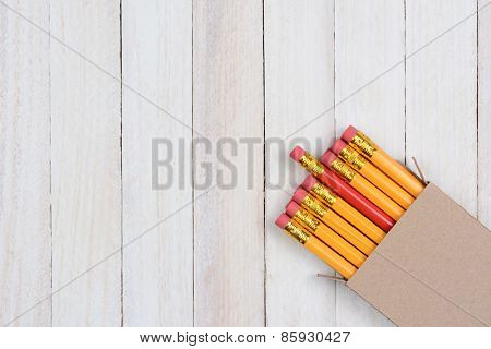 A box of yellow pencils with one red pencil partially pulled out. The plain brown box is in the lower right corner of the frame at an angle.