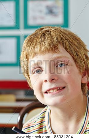 Boy in classroom of elementary school smiling into the camera