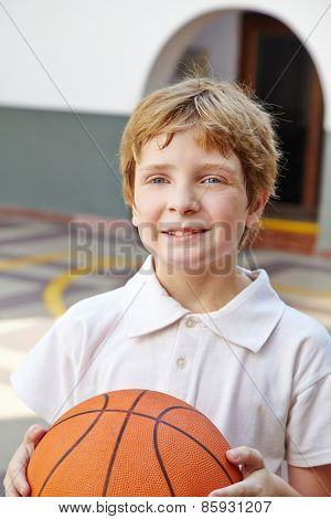 Child with basketball in physical education class in school