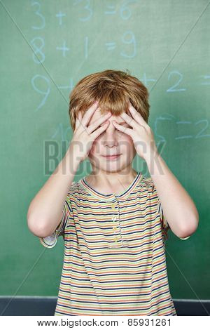 Elementary school student in front of chalkboard in math class