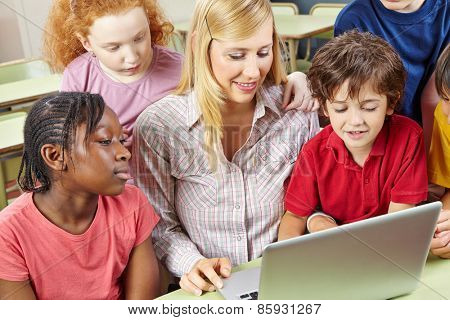 Students and teacher working with laptop computer in elementary school class