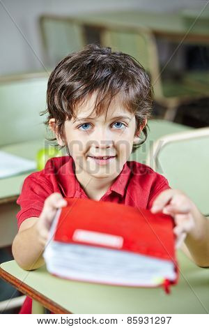 Child in elementary school holding a book in his hands