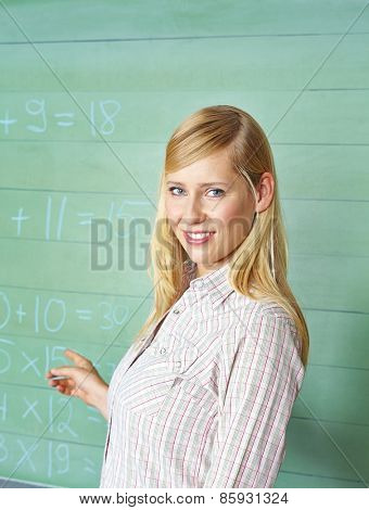 Teacher pointing to chalkboard with math problems in school