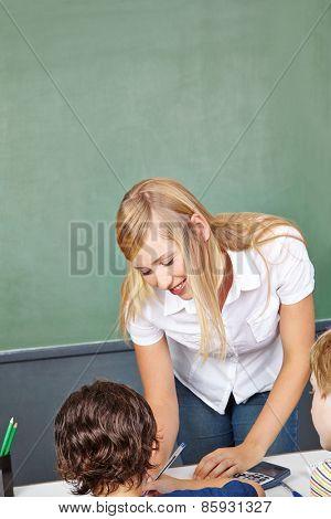 Smiling teacher helping boy in elementary school class