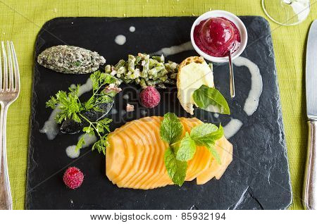 Dramatic Gourmet Lunch On Black Platter with melon, sorbet and salads