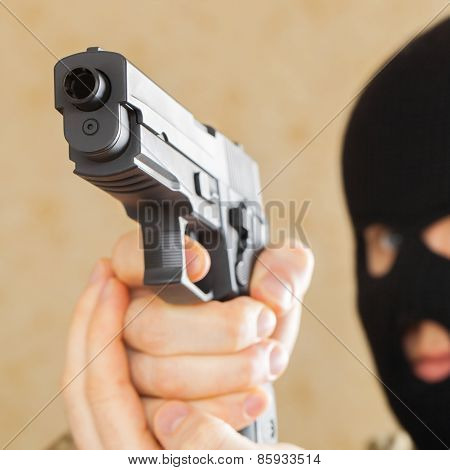 Man In Black Mask Holding Gun And Ready To Use It